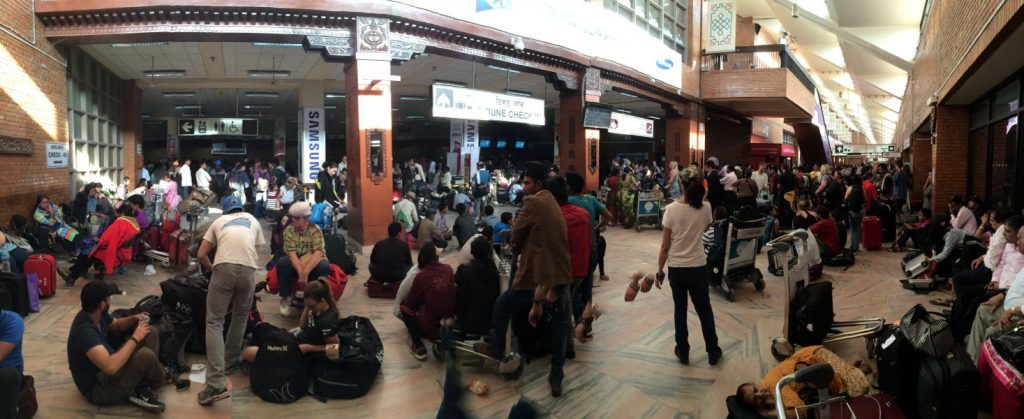 Inside the airport, at the ticket counters.